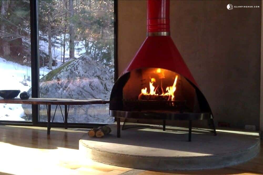 A red woodstove with a blazing fire. A window shows a snowy scene outside.