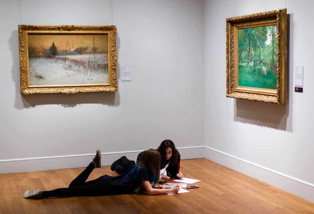 Two teenagers lie on the floor in one of the galleries at the Clark Art Institute in Williamstown, Massachusetts.