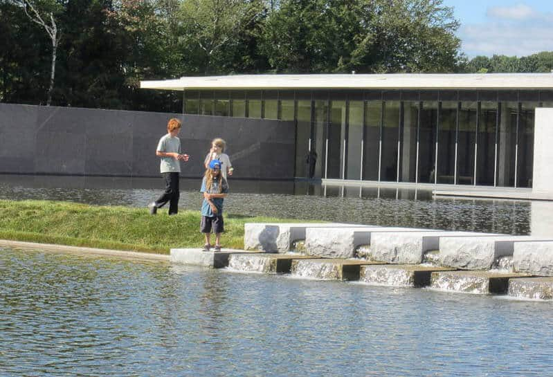 Three kids explore the reflection pool at The Clark in Williamstown, MA.