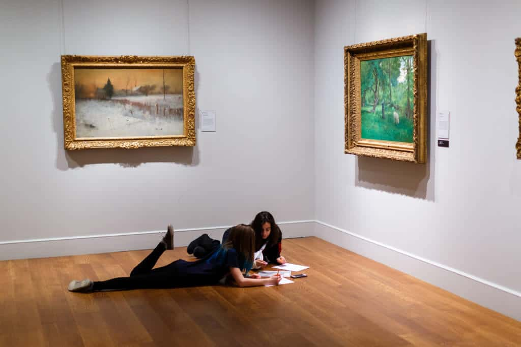 Two teenagers relax on the floor of one of the galleries at The Clark in Williamstown, Massachusetts.