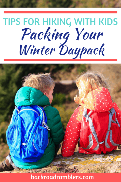Two kids sitting with their backs to the camera. They are wearing colorful clothing and daypacks. Caption reads: Tips for Hiking with Kids. Packing your winter daypack.