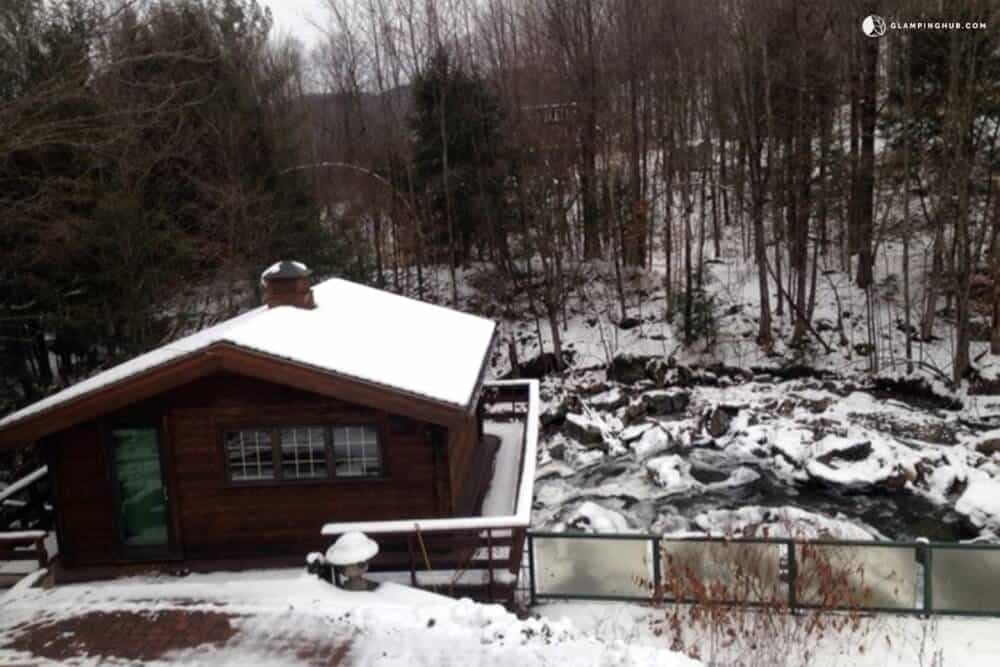 A log cabin perched above a waterfall in Montgomery, Vermont.