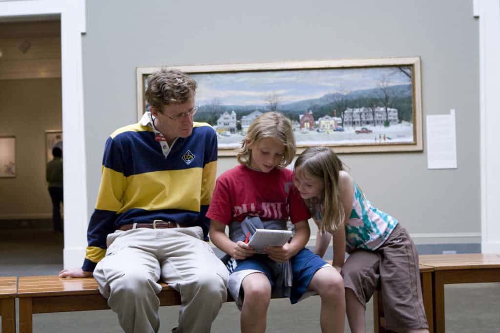 A man sits with two young children at one of the galleries in the Norman Rockwell Museum in Stockbridge, Massachusetts