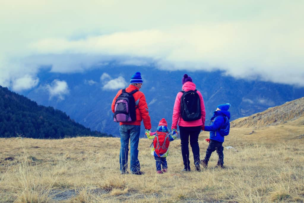 A family is show from behind on a hiking trip in the winter.
