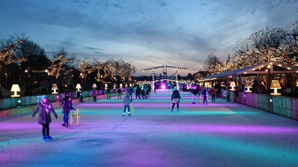 A night scene at an ice skating rink with many skaters and colorful lights.