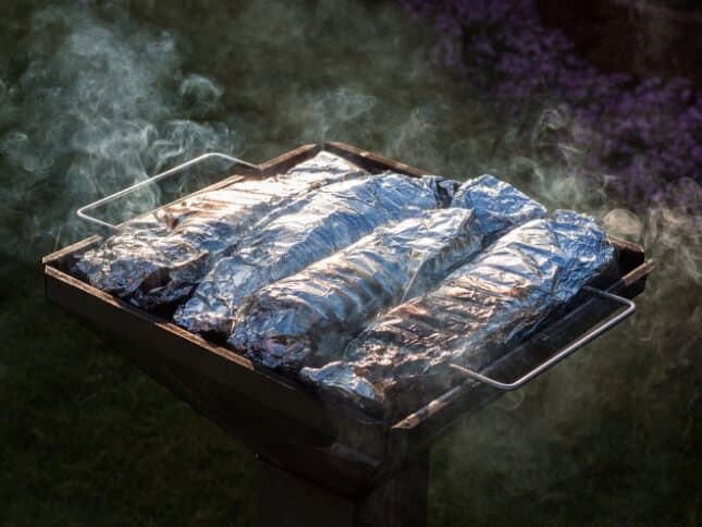 Several quesadillas wrapped in foil on a campfire grill.
