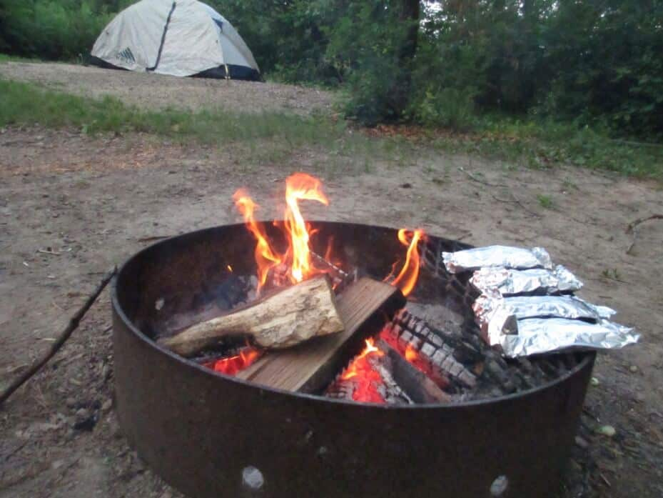 Foil packets roast over a campfire