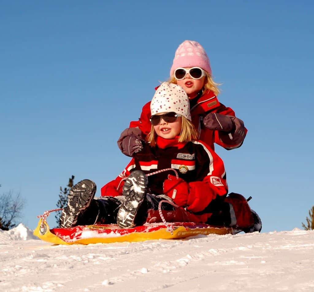 Two girls in winter clothes sit on a sled at the top of a hill.