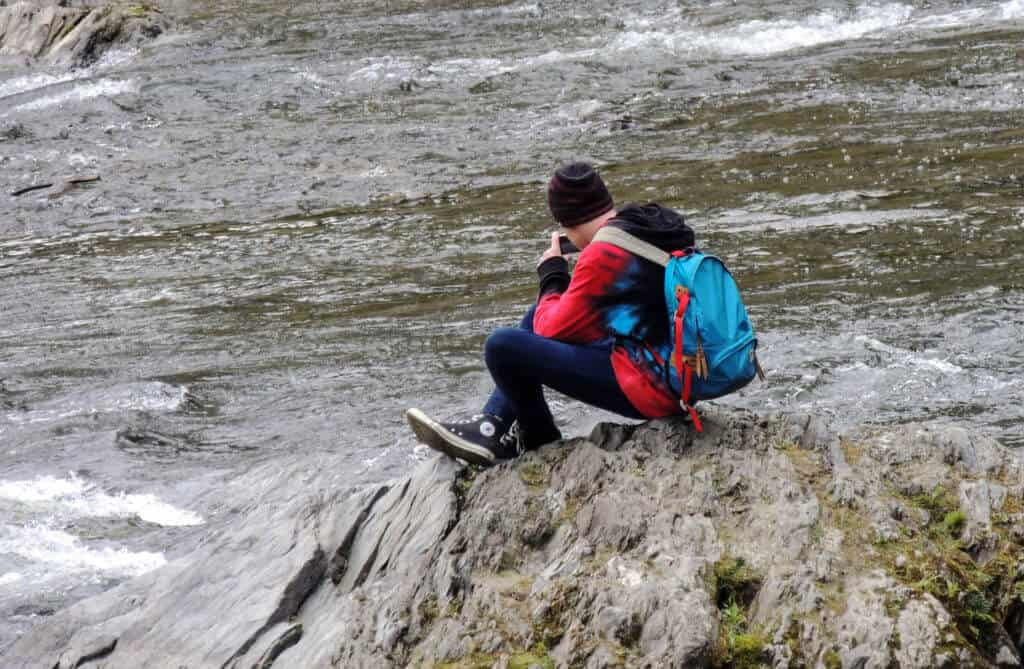 A boy sits on a rock near a stream in the winter. He is wearing colorful clothing and a blue daypack.