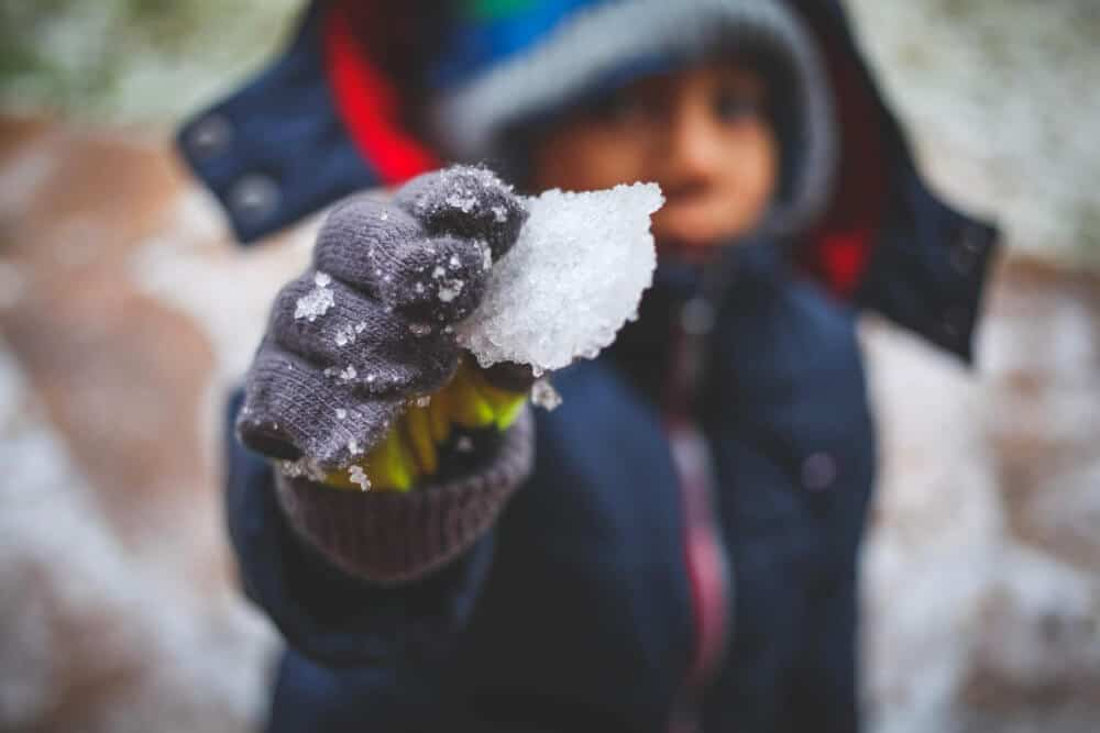 a selective focus capture of a boys mittened hand holding a bit of snow.