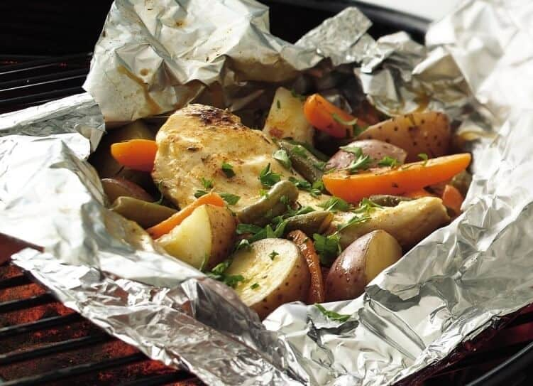 A foil packet with chicken and veggies sitting on the grill with coals underneath.