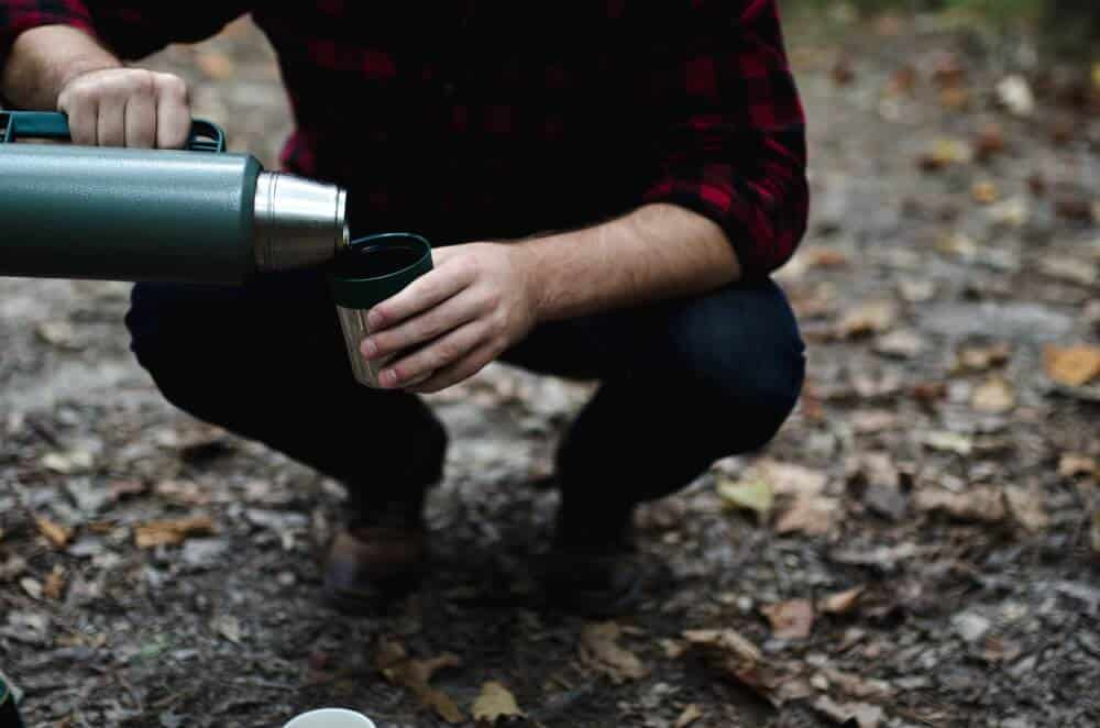 A man kneels outside pouring hot chocolate from a thermos into a mug.
