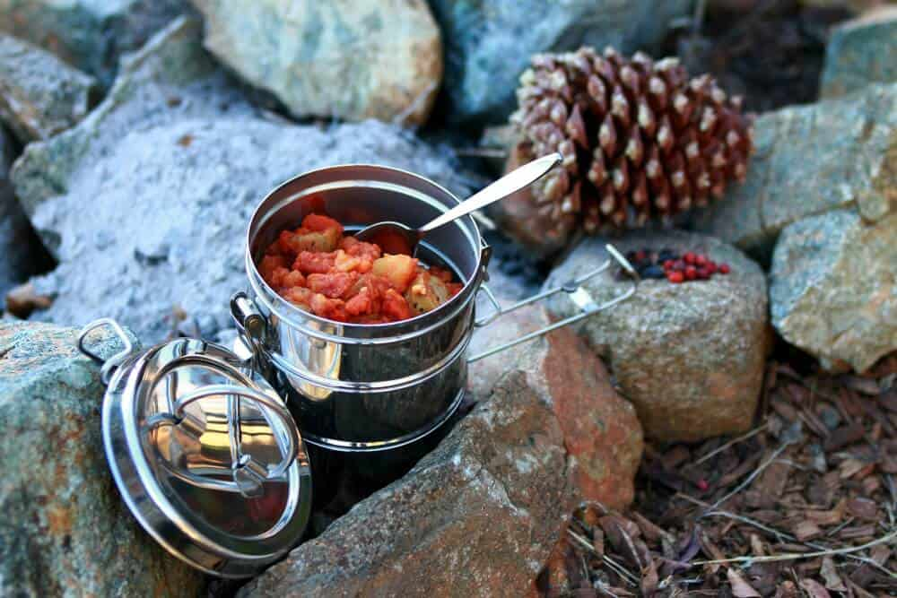 Preparing a car camping spice kit. A camp meal with a spoon in it, sitting next to a campfire.
