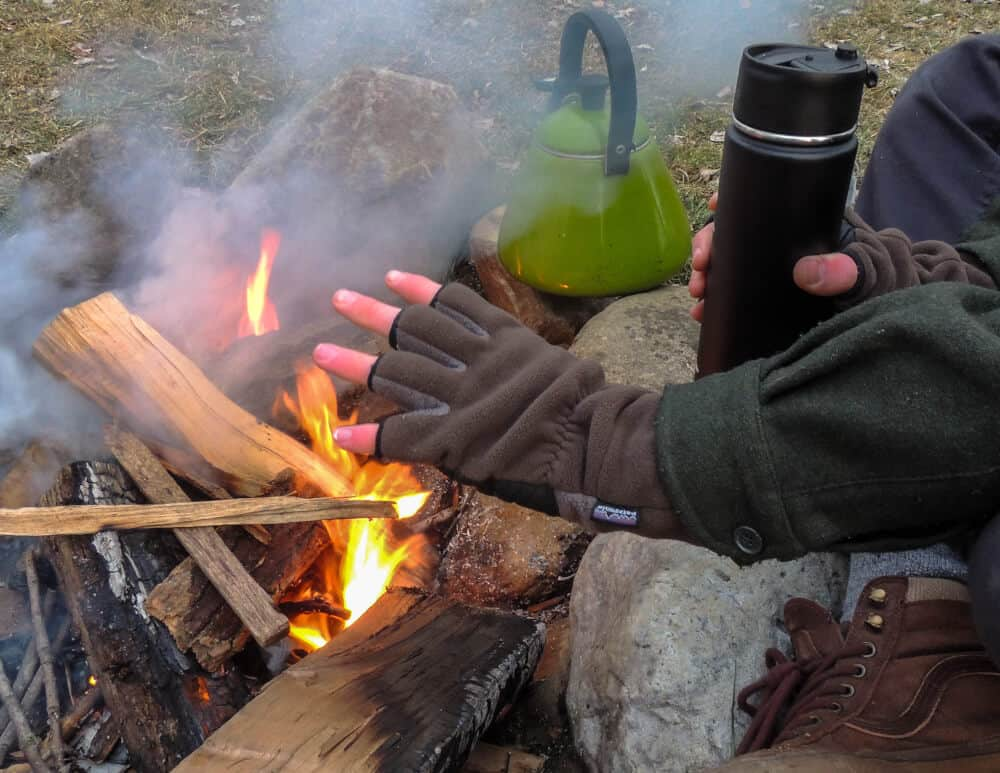 a close up of a campfire with hands warming up and a tea kettle.