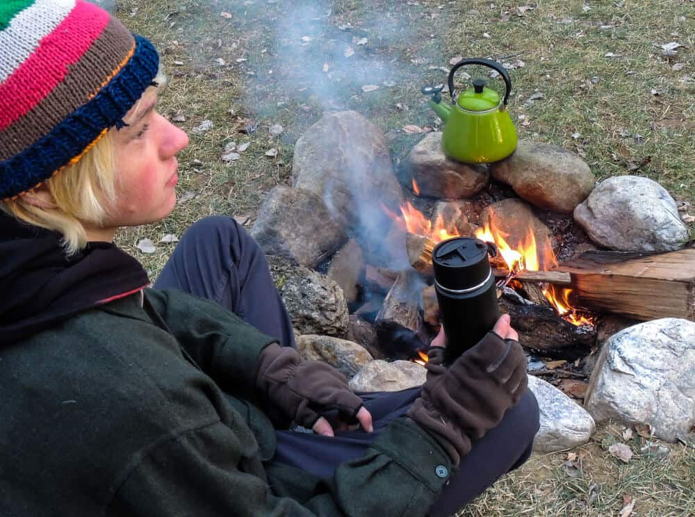 A young man sits near a campfire enjoying a hot drink.