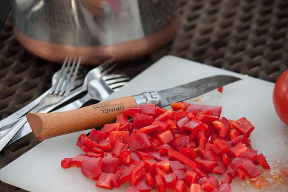 A cutting board with chopped red peppers on it, next to a folding pocket knife and four forks.