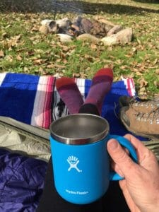 A view from inside a tent of a travel coffee mug, socked feet, and a pair of hiking boots.