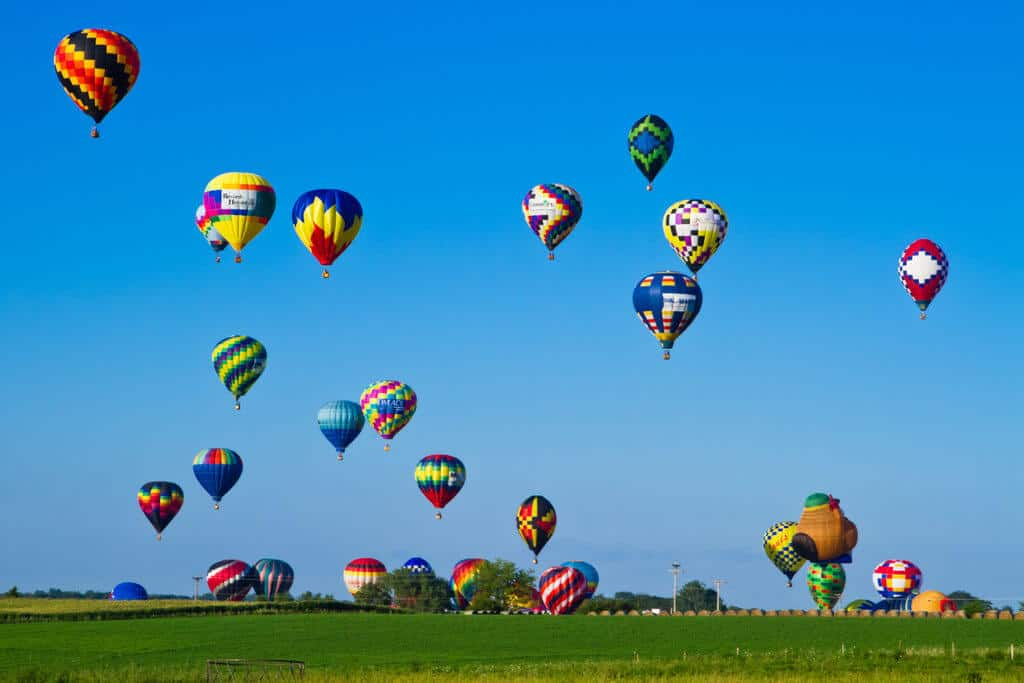 Several hot air balloons, some on the ground some rising into a deep blue sky.