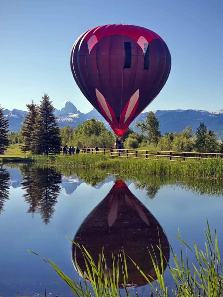 A gorgeous hot air balloon rises over a lake with the Tetons in the background.