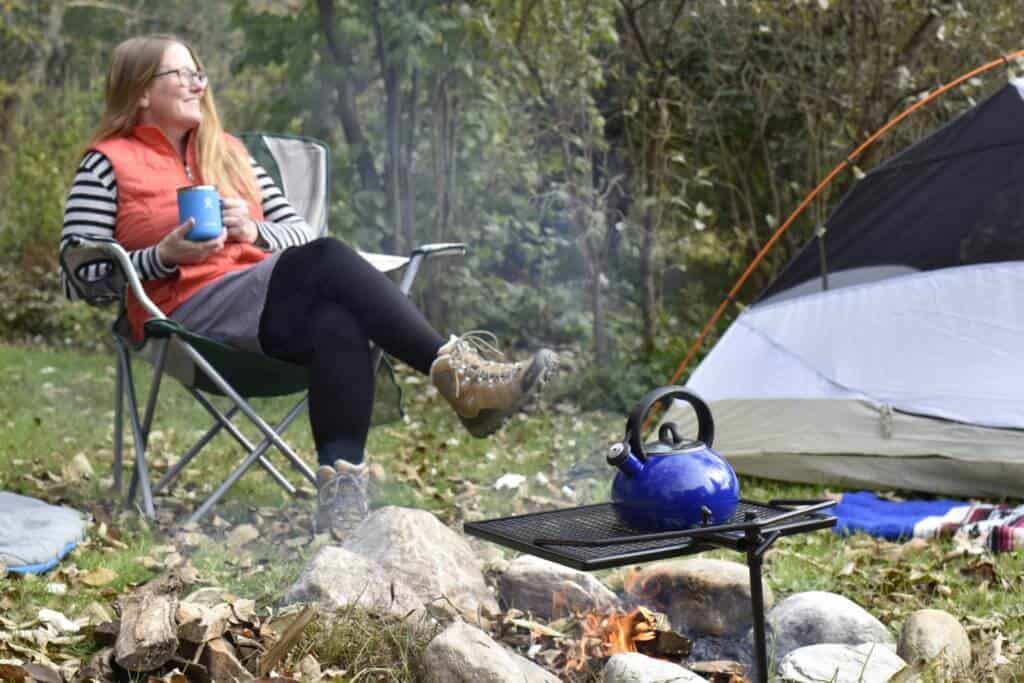 A woman sits in a camping chair next to a tent and a campfire. She is holding a mug of camping coffee and she is smiling because coffee is delicious.