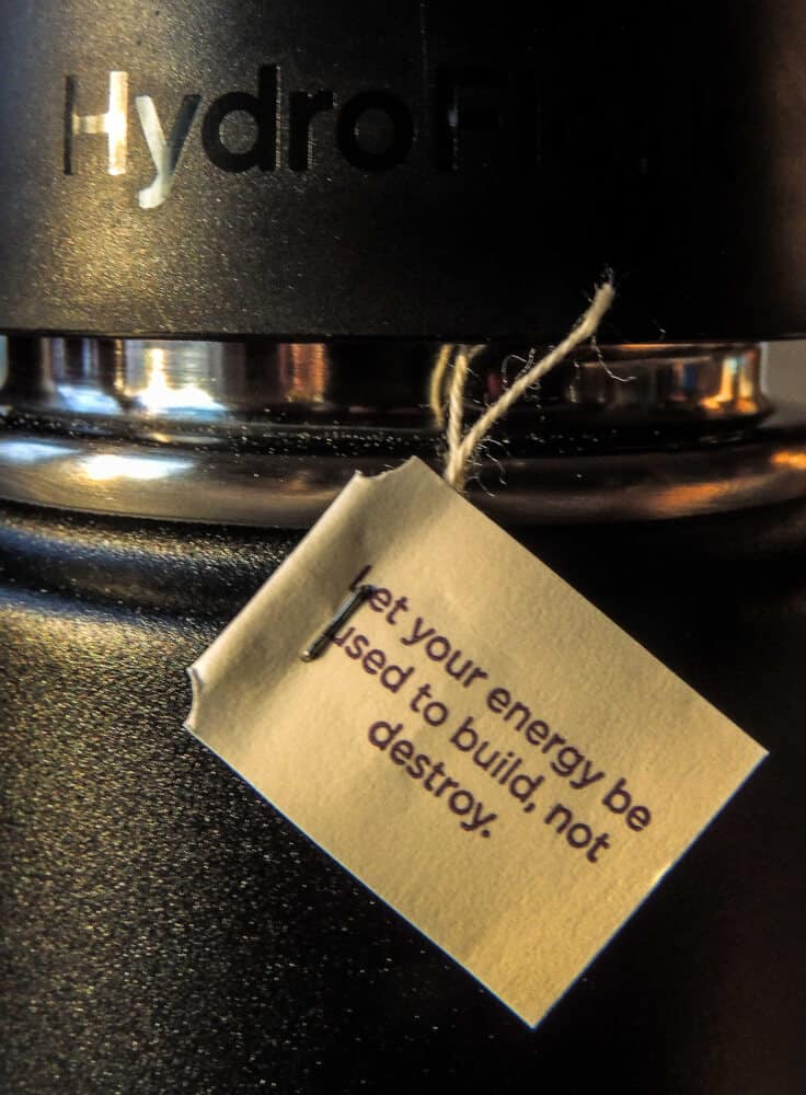 A black Hydro Flask travel mug with a tea bag hanging off the side. The note says: Let your energy be used to build, not destroy.