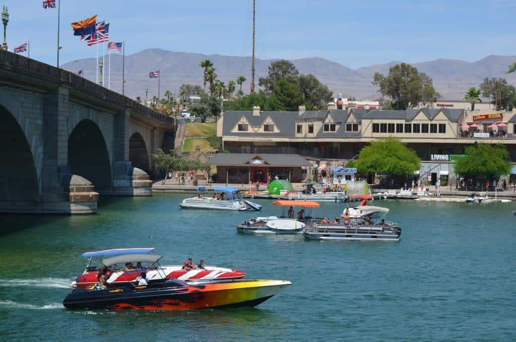 Motor boats and pontoon boats cruise under the London Bridge in Lake Havasu City.