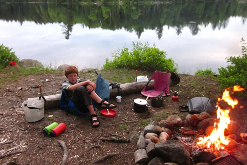 A boy sits near a campfire surrounded by camp dishes. There is a lake in the background.