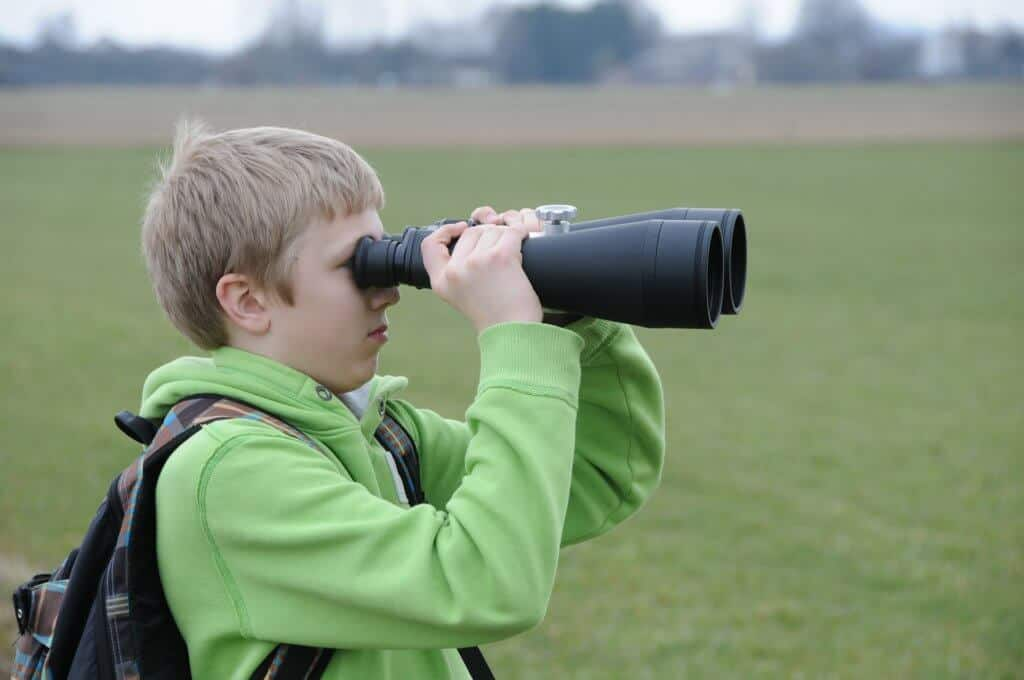 A boy looks through a pair of binoculars.