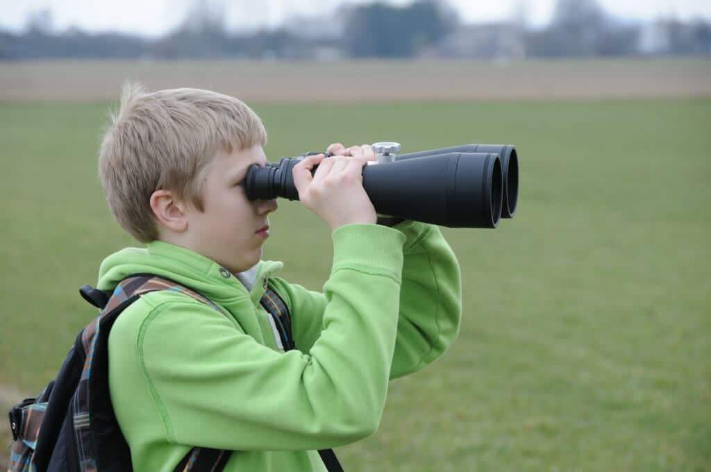 A boy looks through a pair of binoculars.