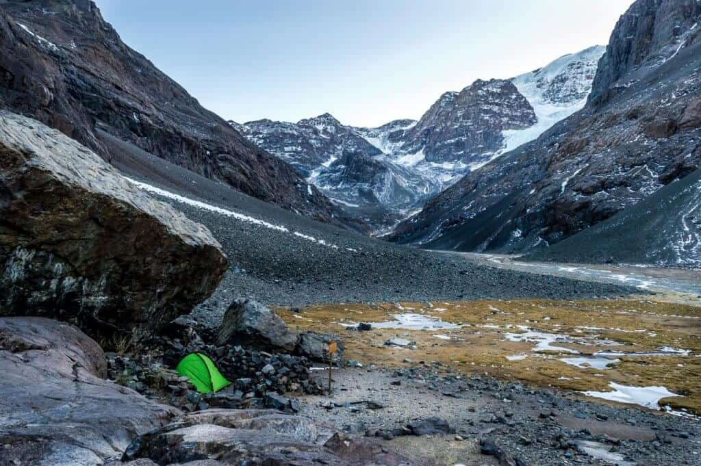 A green tent nestled into a hillside among snowcapped peaks during a spring camping trip.
