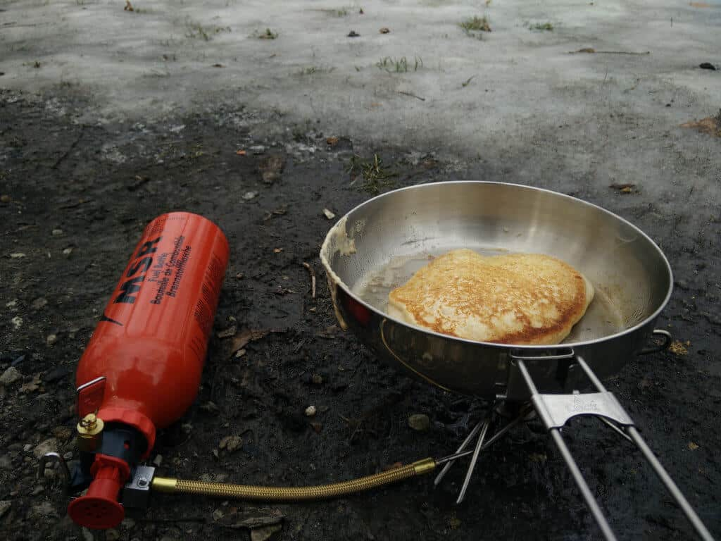 A pancake cooks in a frying pan over a small camping stove.