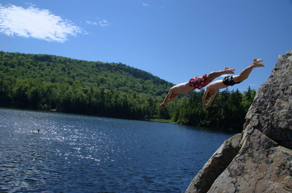 Two boys dive from a cliff into the waters of Little Rock Pond in Vermont