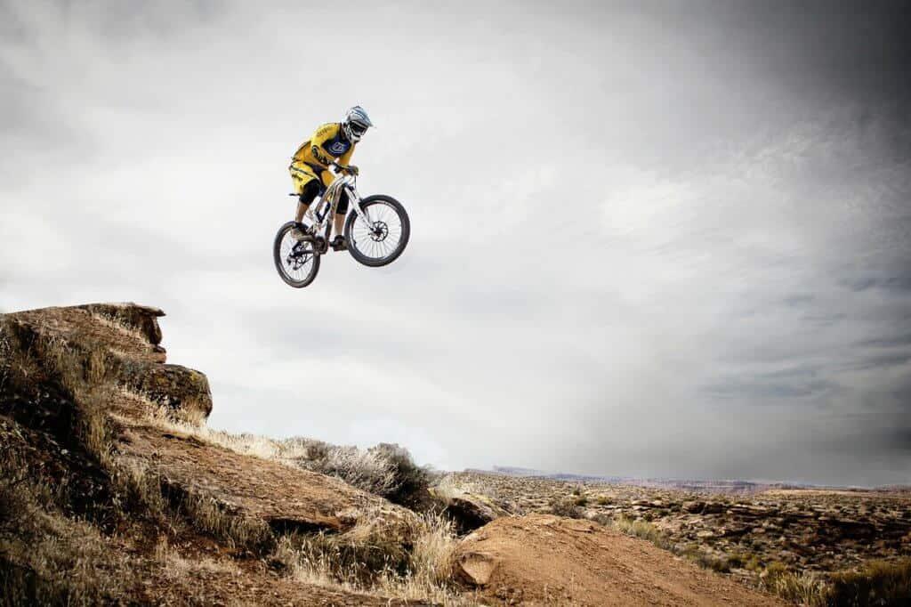 A mountain bike flies over a cliff on a mountain biking trail in Utah
