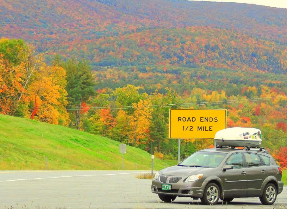 A grey Pontiac Vibe with a cargo carrier on top. Fall foliage in the background and a yellow sign that says,