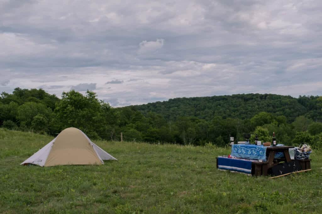 A tent and a picnic table set up in a Vermont field.