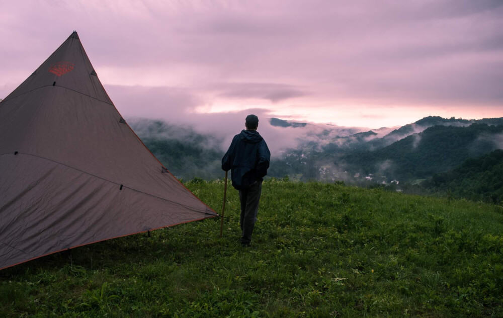 A man stands next to a tent watching the sunset