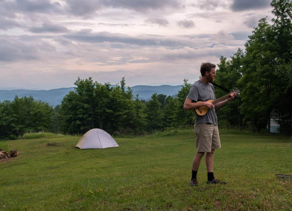 Eric plays his travel guitar in front of our little tent at Mountain Home Farm.