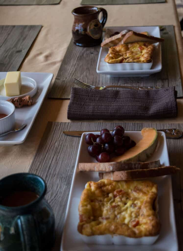 A table set with breakfast - omelets, grapes, toast, and melons
