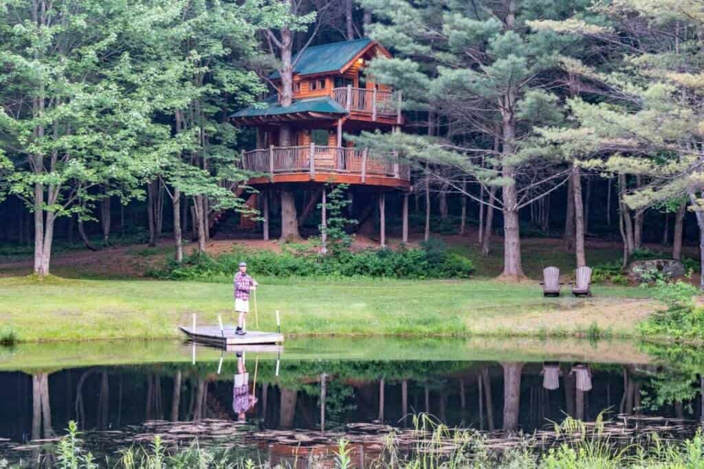 A man stands on a dock in front of a two-story treehouse in Vermont.