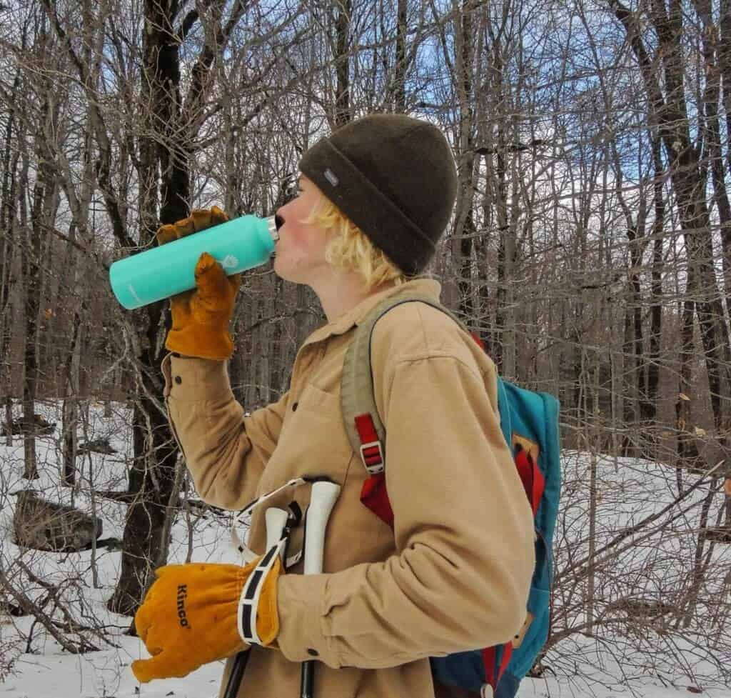 A teenager drinks from a turquoise water bottle while skiing in the woods.