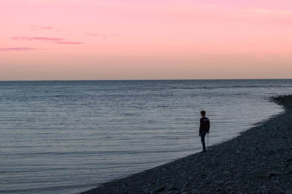A boy stands on the edge of the Bay of Fundy watching the tides go out.