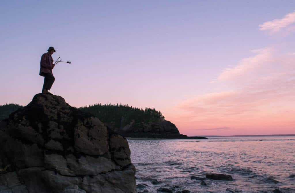 A boy stands on a rock looking out at the Bay of Fundy tides in Fundy National Park.