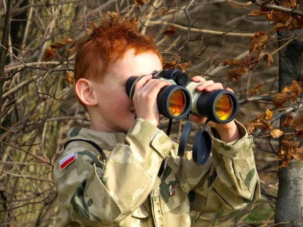 A young child holds binoculars up to his eyes to watch the birds