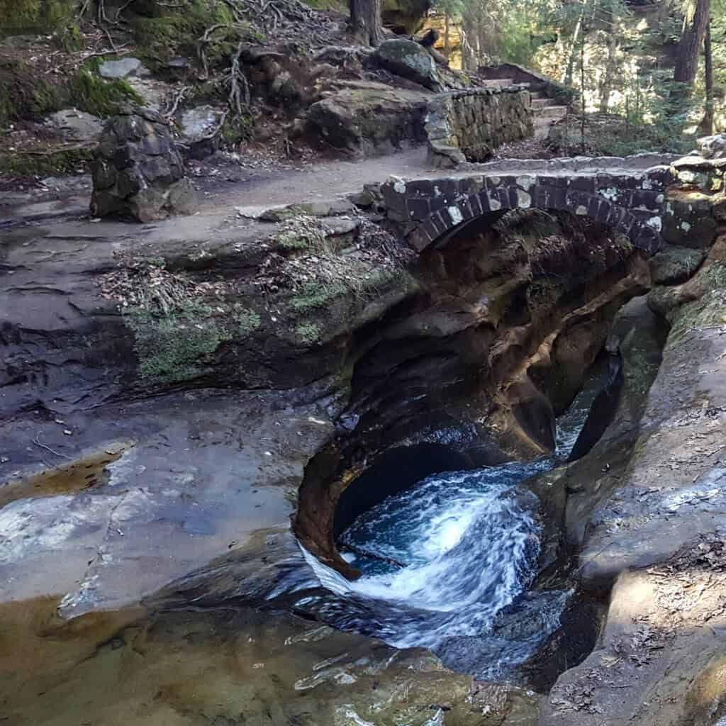 A small foaming river rushing through a rock crevice in Hocking Hills State Park. There is a stone bridge/hiking path over the river.