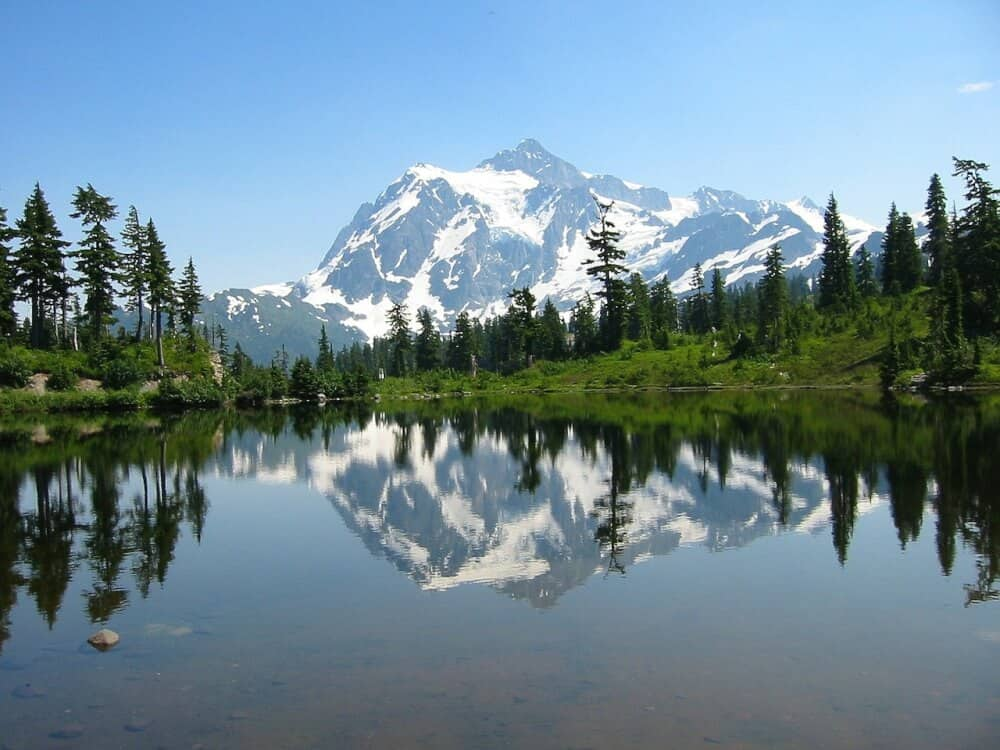 a snow-capped mountain reflected in a lake in North Cascades National Park