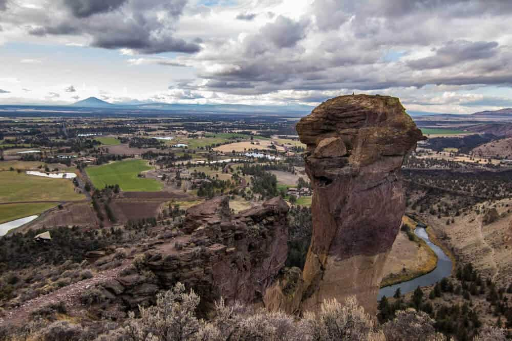 a sweeping vista of a large rock formation and the valley below - Smith Rock State Park
