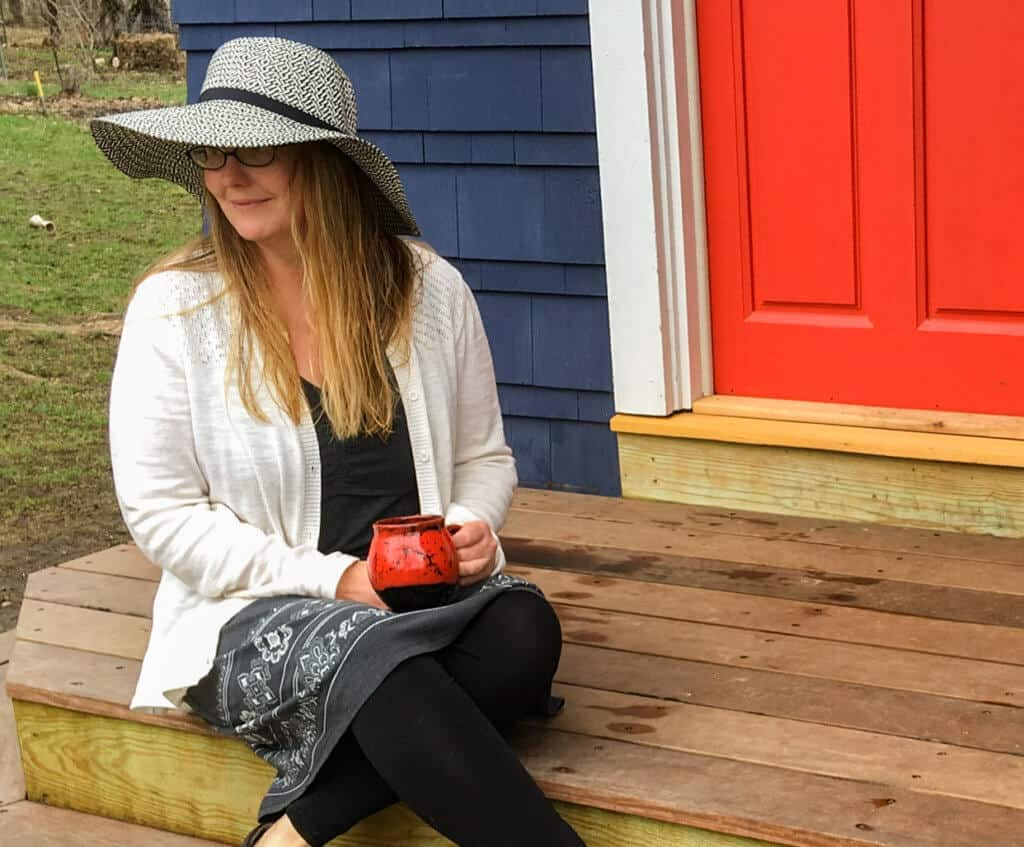 A woman sitting on a porch wearing a black dress, white sweater, and black and white hat
