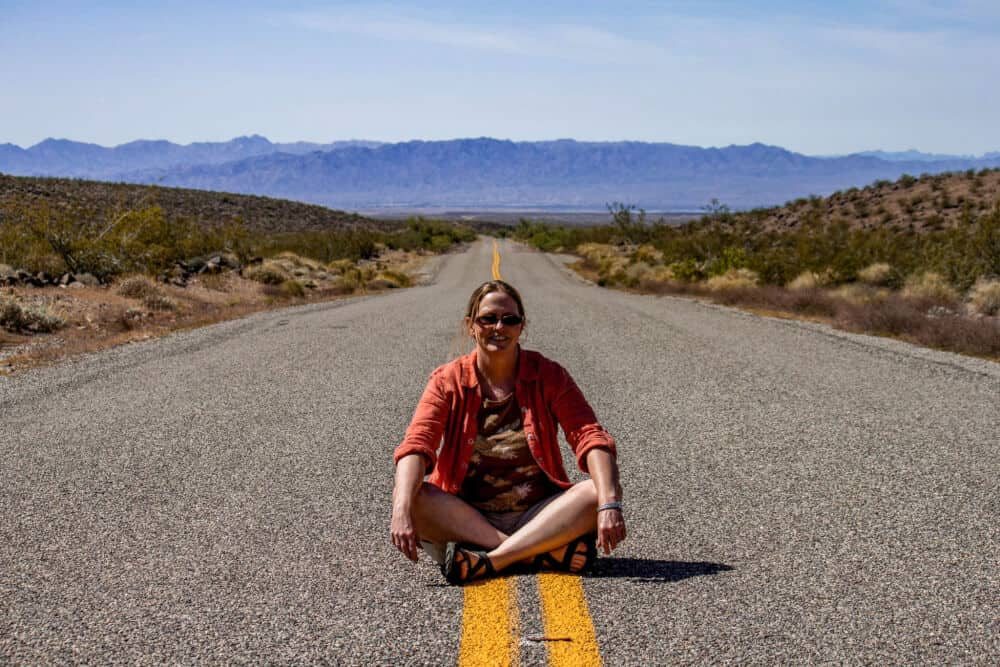 A woman sitting in the middle of the road on route 66 in Oatman, Arizona. There are mountains in the background.