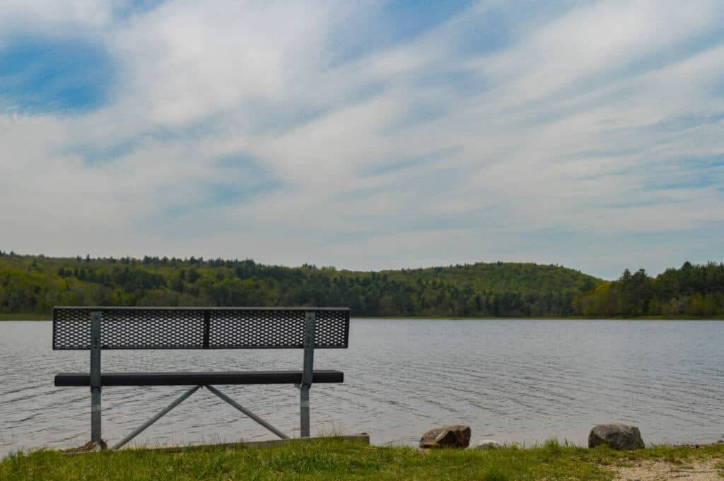 A lone bench overlooking McDowell Dam in Peterborough, NH