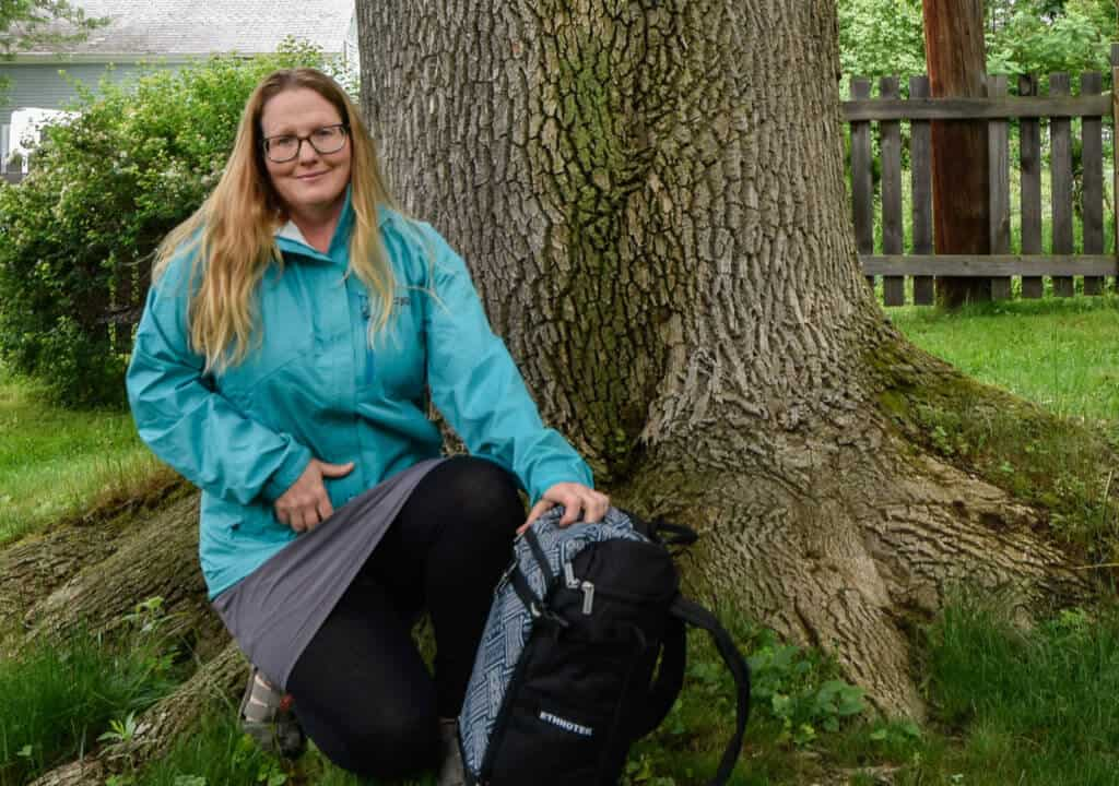 Me wearing a turquoise jacket next to a tree.